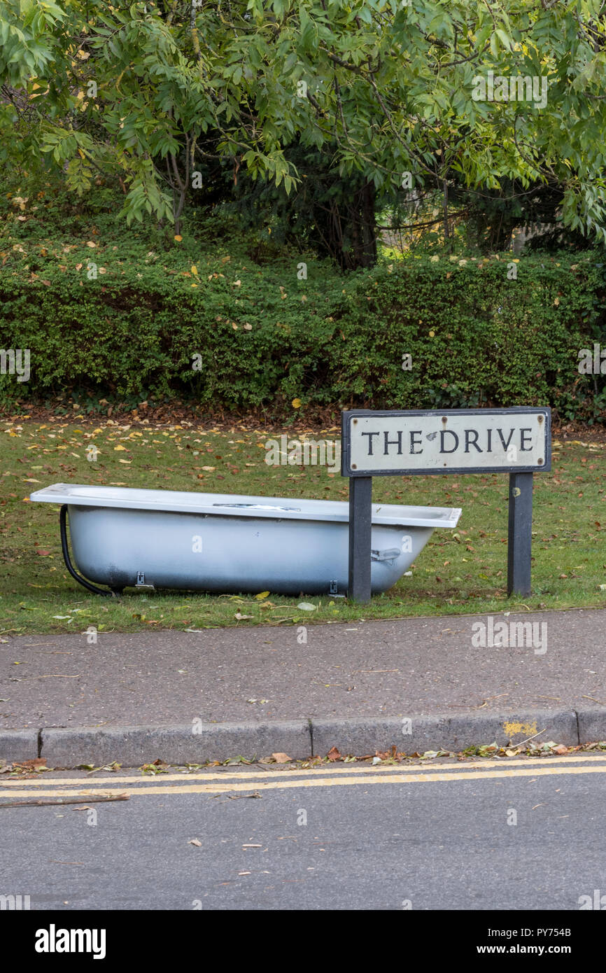 fly tipping discarded bath tub left on a grass verge in a tow. rubbish tipped by the side of the road by fly or irresponsible ignorant trash tippers. - Stock Image