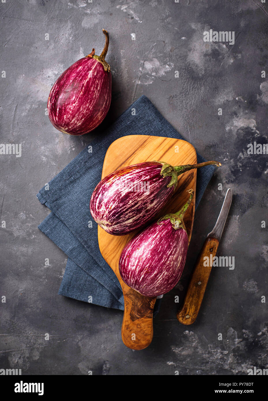 Fresh striped purple aubergines on grey background - Stock Image
