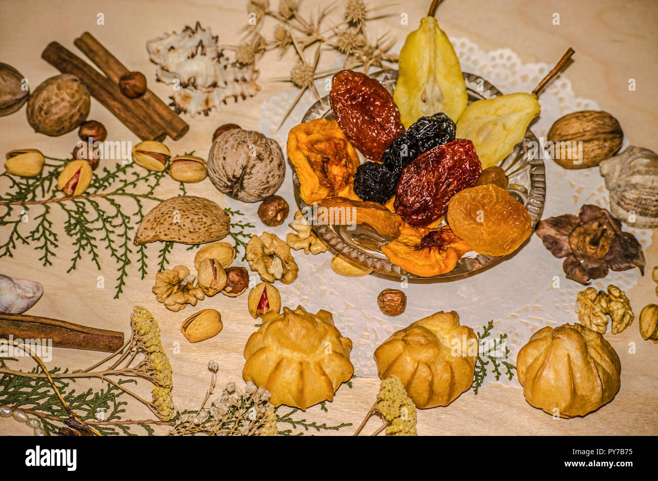 Dried frui in crystal rosette, nuts, pistachio, hazelnut, with eclairs, cinnamon surrounded by dried plants and shells on a figured shaped napkin - Stock Image
