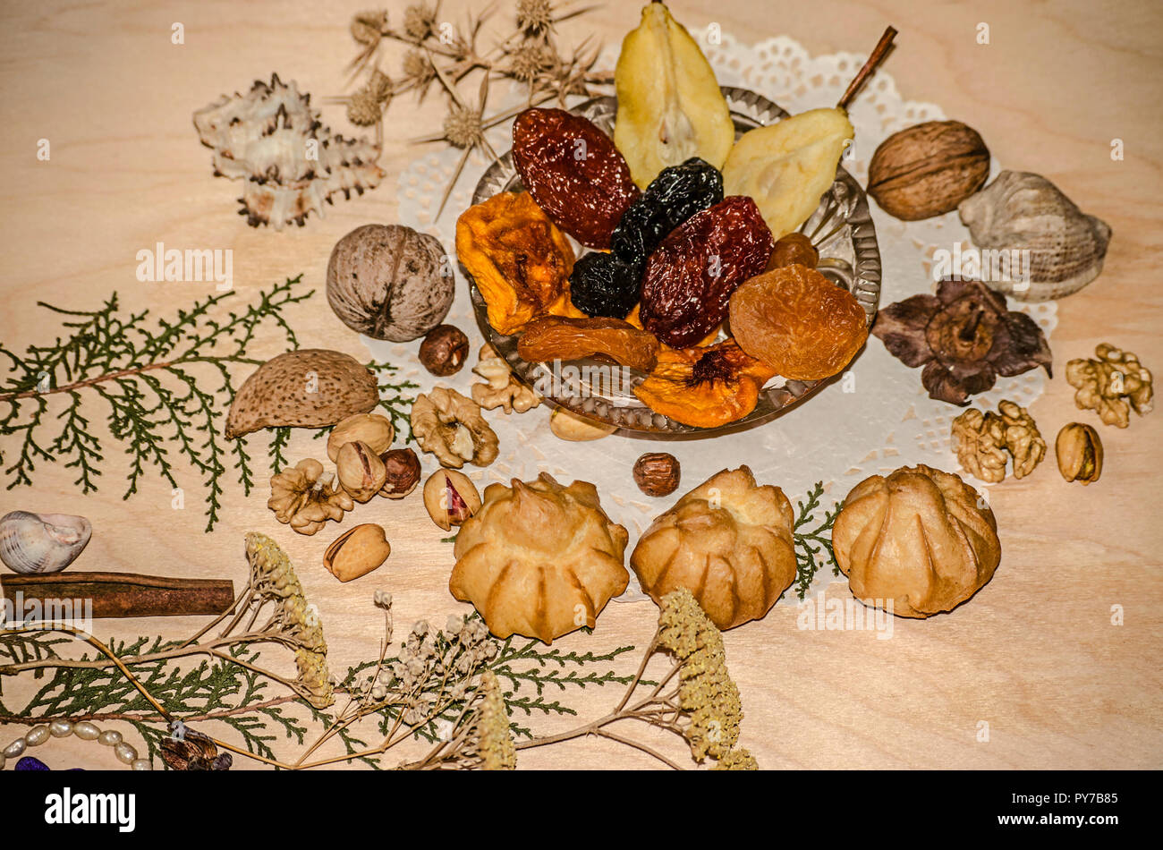Nuts,pistachios,hazelnuts near a crystal rosette with dried fruit,eclairs,cinnamon,surrounded by dried plants and shells on a figured napkin - Stock Image