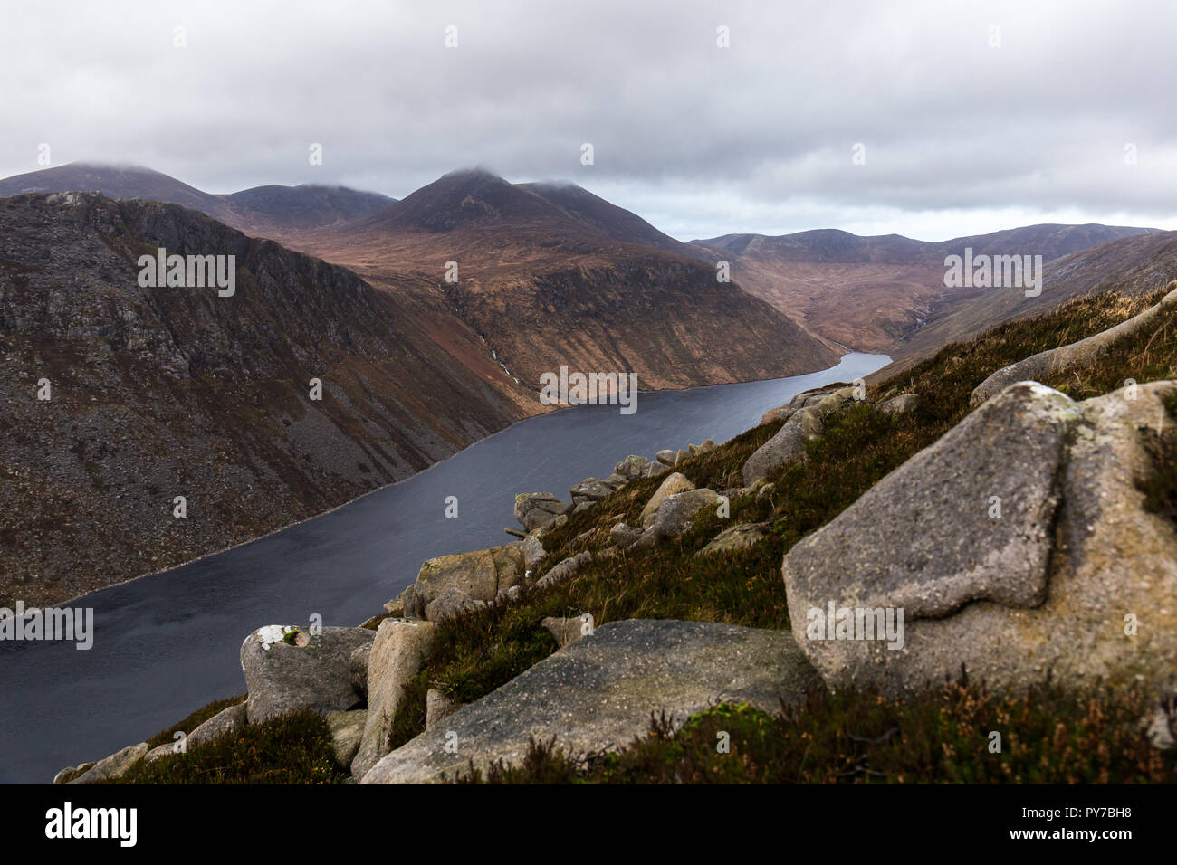 View of Ben Crom mountain and reservoir looking towards Slieve Bearnagh in cloud from lower slopes of Slieve Binnian. Doan mountain on left. Mourne Mo - Stock Image