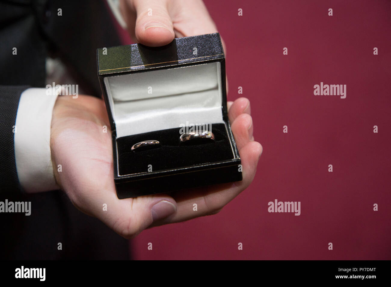 wedding rings in ring box held in best mans hand right before the wedding ceremony - Stock Image