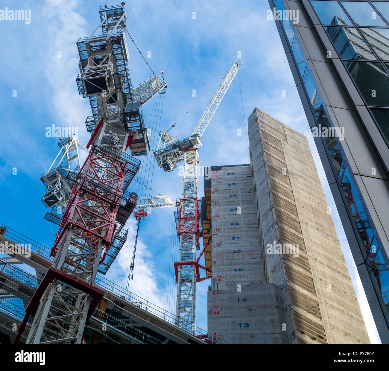 Three tower cranes at construction site in the City of London against a blue sky - Stock Image
