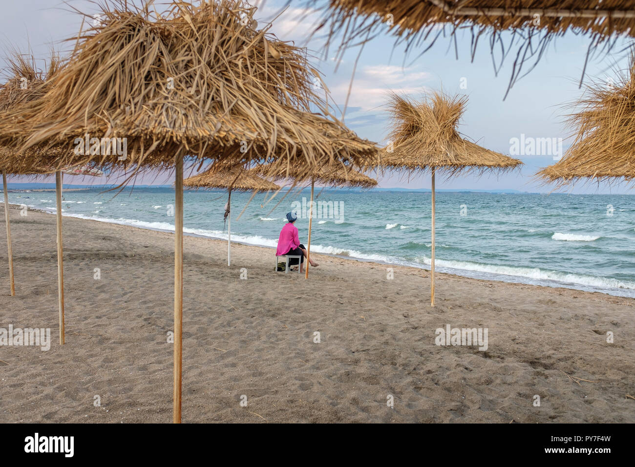 Woman contemplating  on the deserted beach on a late summer afternoon - Stock Image