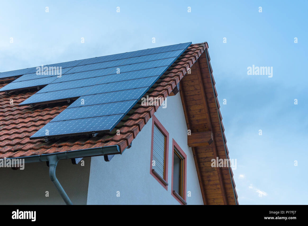 Solar panel construction on red roof of a house - Stock Image