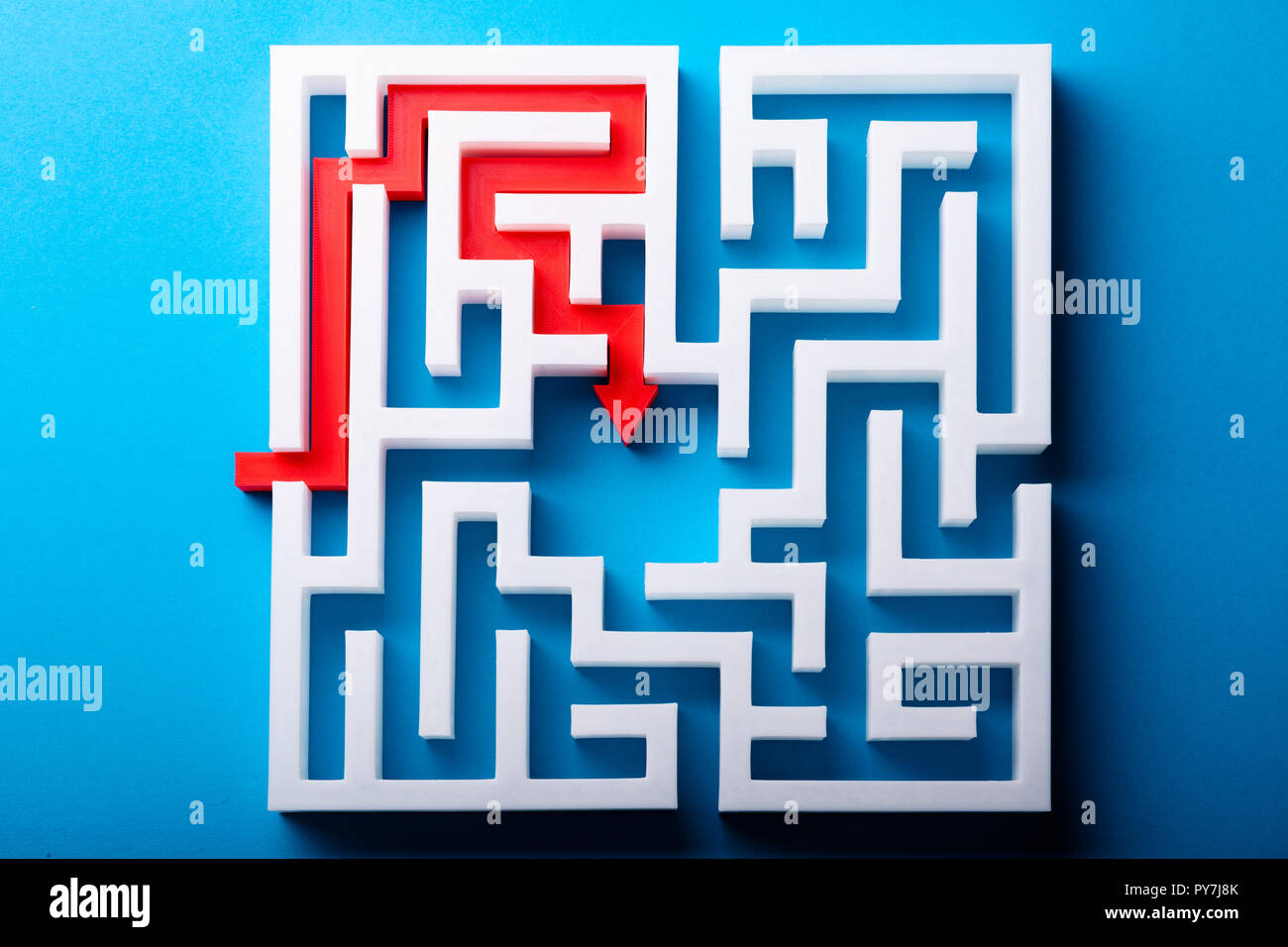 Elevated View Of Red Arrow At The Center Of White Maze On Blue Surface - Stock Image