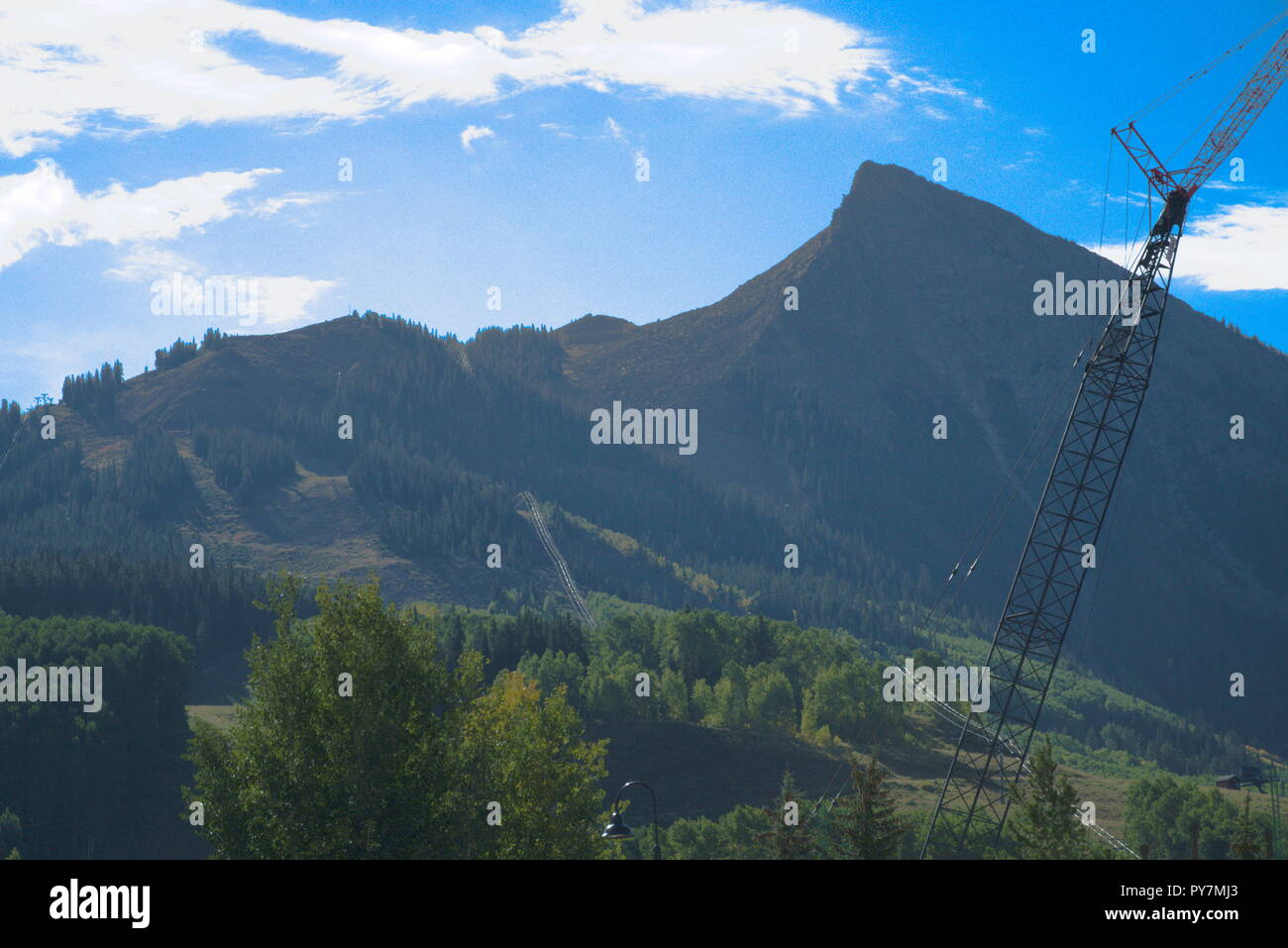 Crested Butte mountain with a crane and some trees in front, with a blue sky and white clouds. - Stock Image