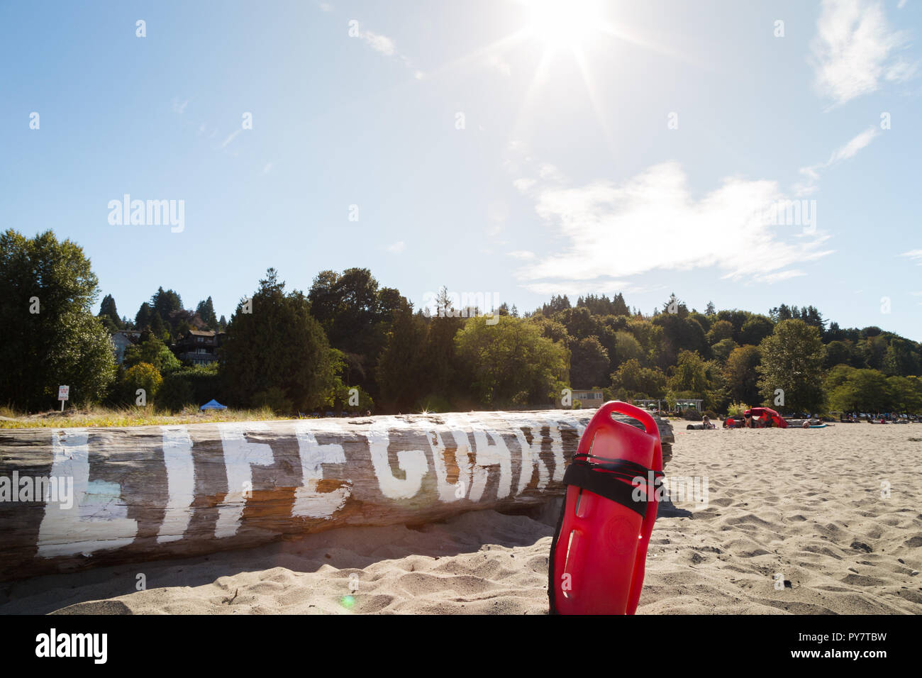 8f66c4b4199 A lifeguard buoy in the sand in front of a log with lifeguard written on it