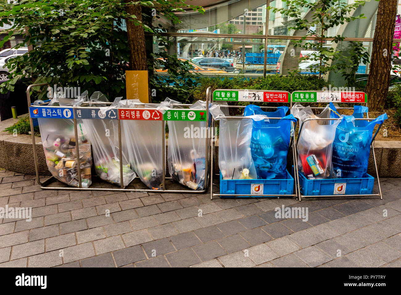 Seoul, South Korea - June 20, 2017: Waste sorting containers with colored inscriptions for plastic, glass bottles and paper in the downtown in Seoul. Stock Photo