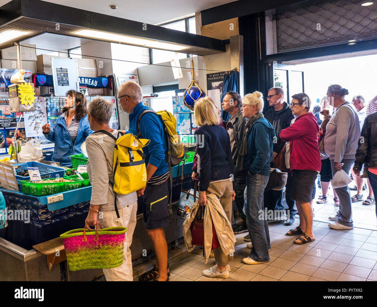 BRETON FEMALE FISHMONGER FISH MARKET CONCARNEAU HALLES Concarneau Busy Fish Market stall with fresh local crustacea  display for sale Brittany France - Stock Image