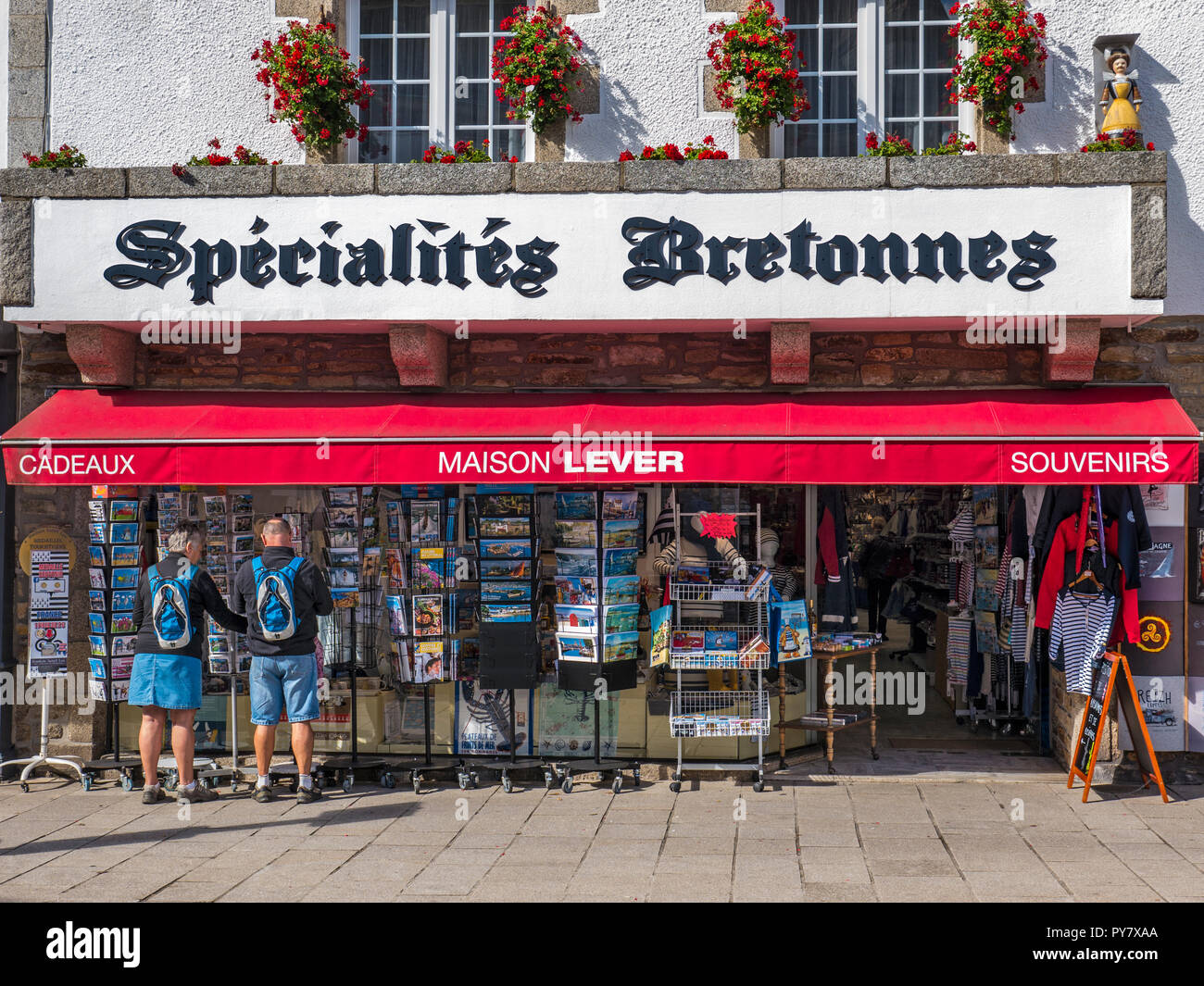 PONT AVEN TOWN BRITTANY FRANCE Pont-Aven village shopping centre with colour coordinated couple browsing holiday postcards Finistère  Brittany France - Stock Image