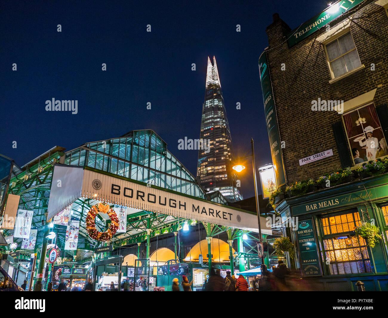 Christmas Borough Market exterior entrance & Christmas shoppers, lights night with Christmas wreaths London Shard Tower behind Southwark London UK - Stock Image