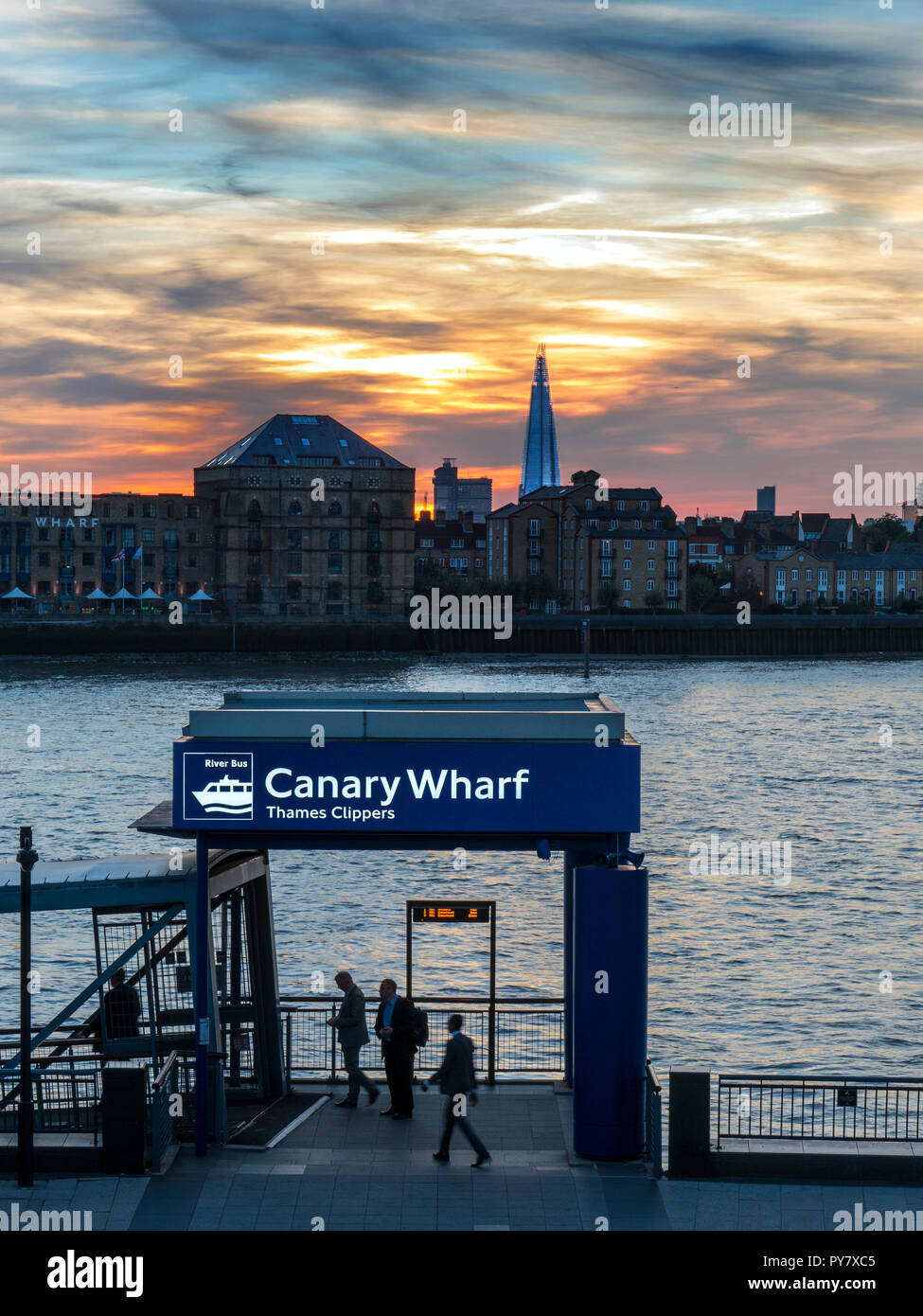 CANARY WHARF COMMUTERS Pier embarkation point for Thames Clipper River boats, Columbia Wharf Shard, & City buildings behind, Canary Wharf London UK - Stock Image
