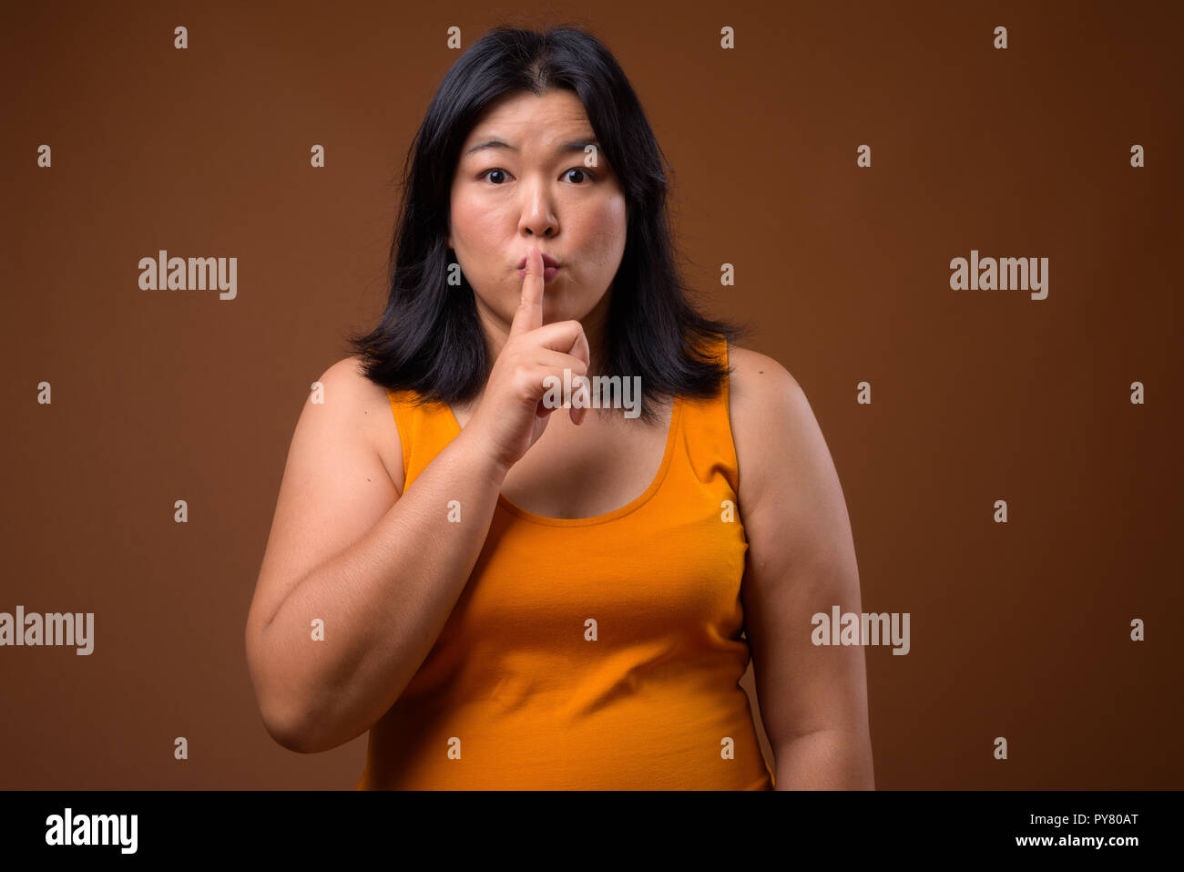 Beautiful overweight Asian woman hush with finger on lips - Stock Image