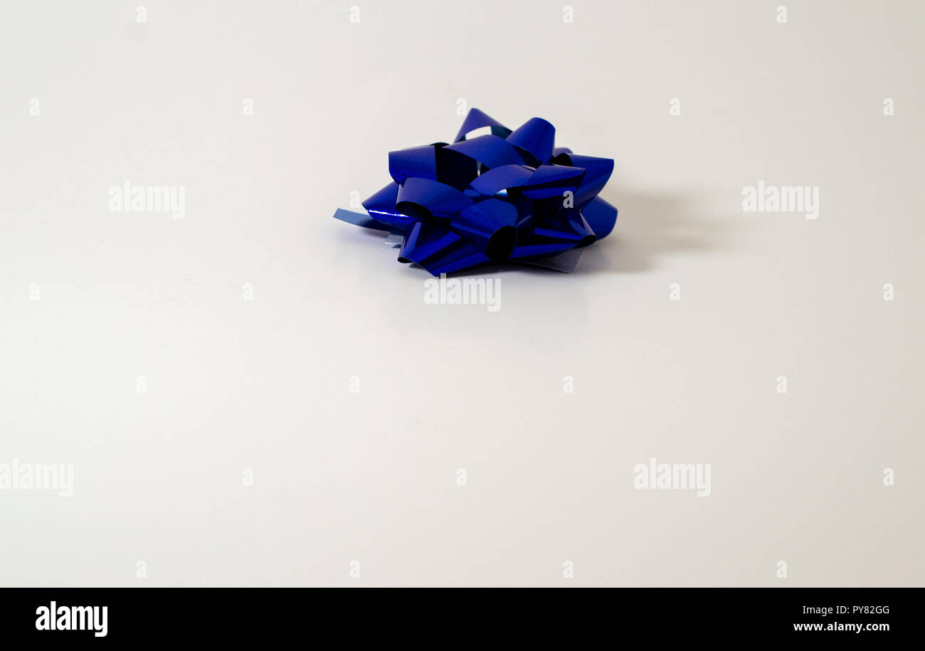 One (1) Blue Christmas Holiday Bow Ribbon on light background. Plenty of room for Christmas or holiday copy. - Stock Image