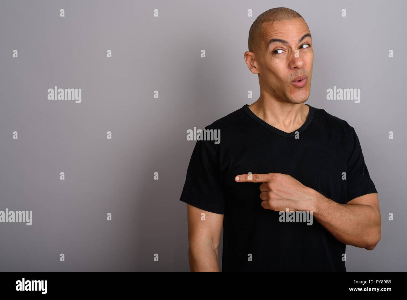 Handsome bald man looking disgusted and pointing finger - Stock Image
