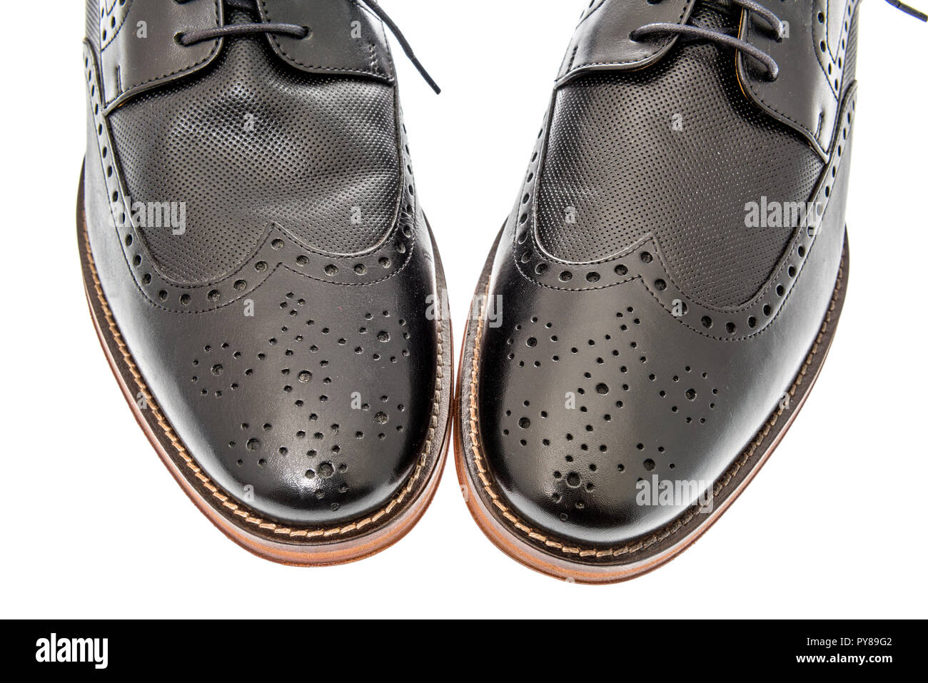 7c47e52c A close-up shot of a pair of mens black wingtip dress shoes on an isolated  background