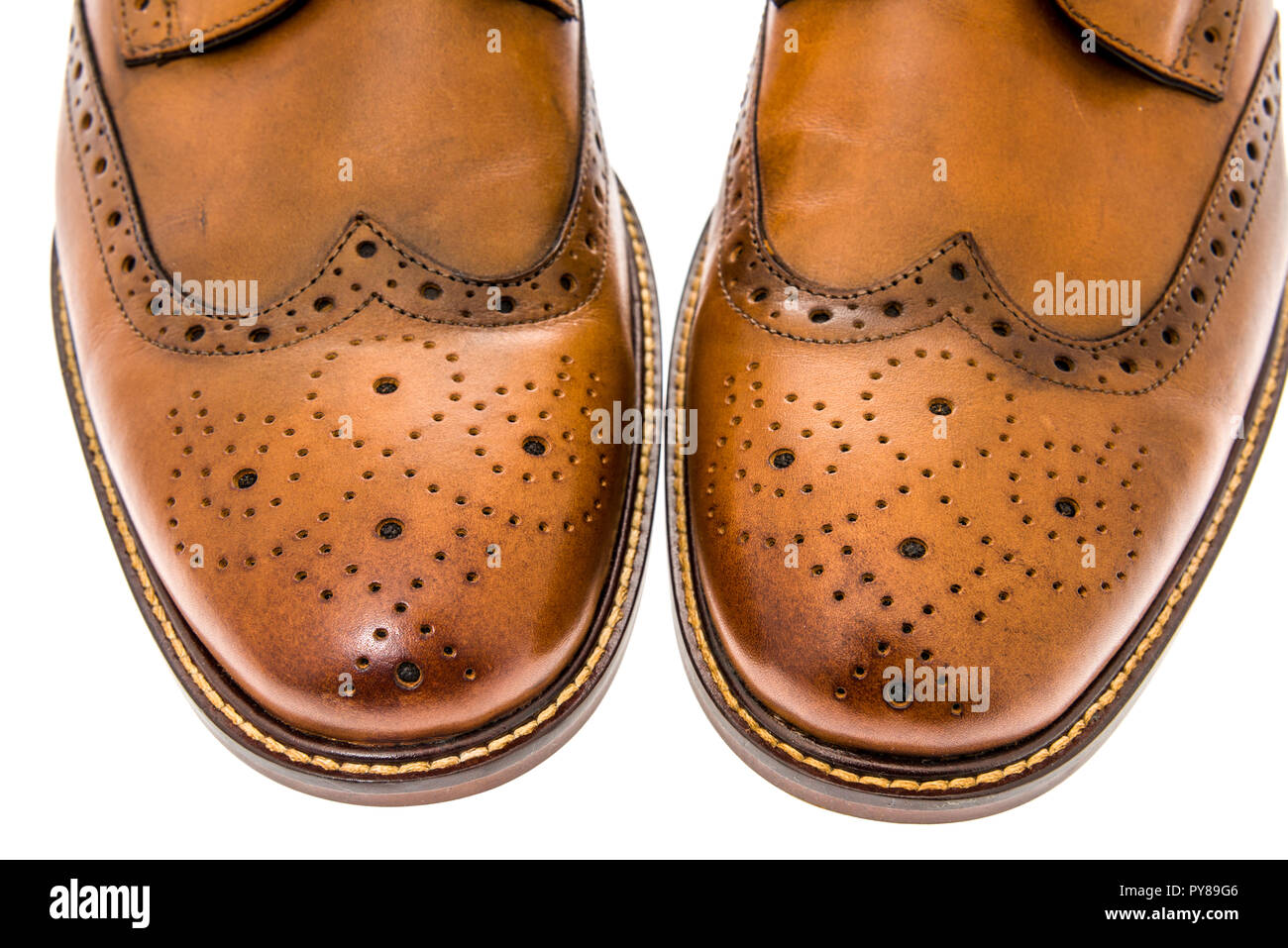 8bd87d05 A close-up shot of a pair of mens brown wingtip dress shoes on an isolated  background