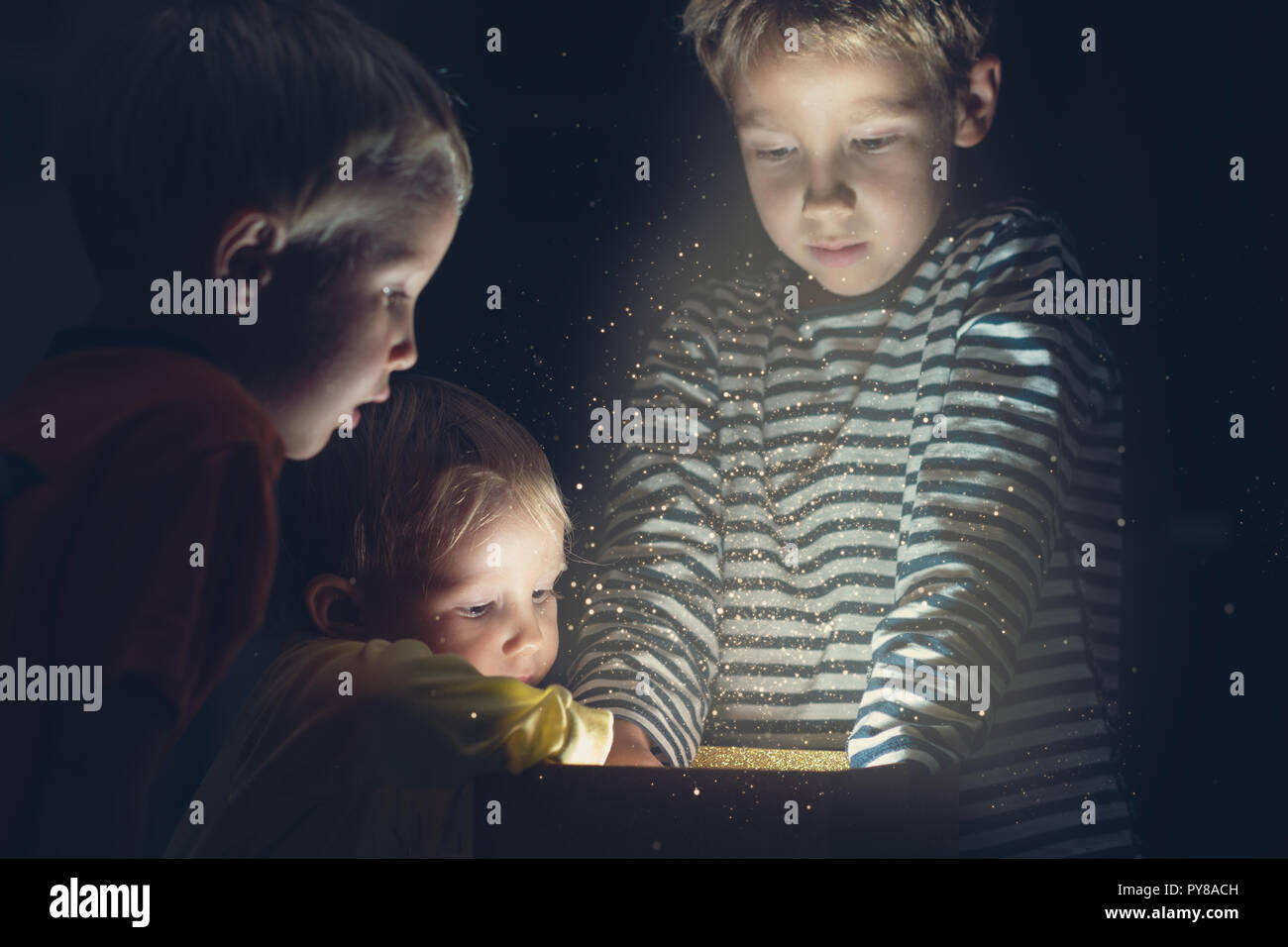 Retro image of holiday magic with three toddler kids reaching in golden gift box with sparkling light and glitters shinning from it. - Stock Image