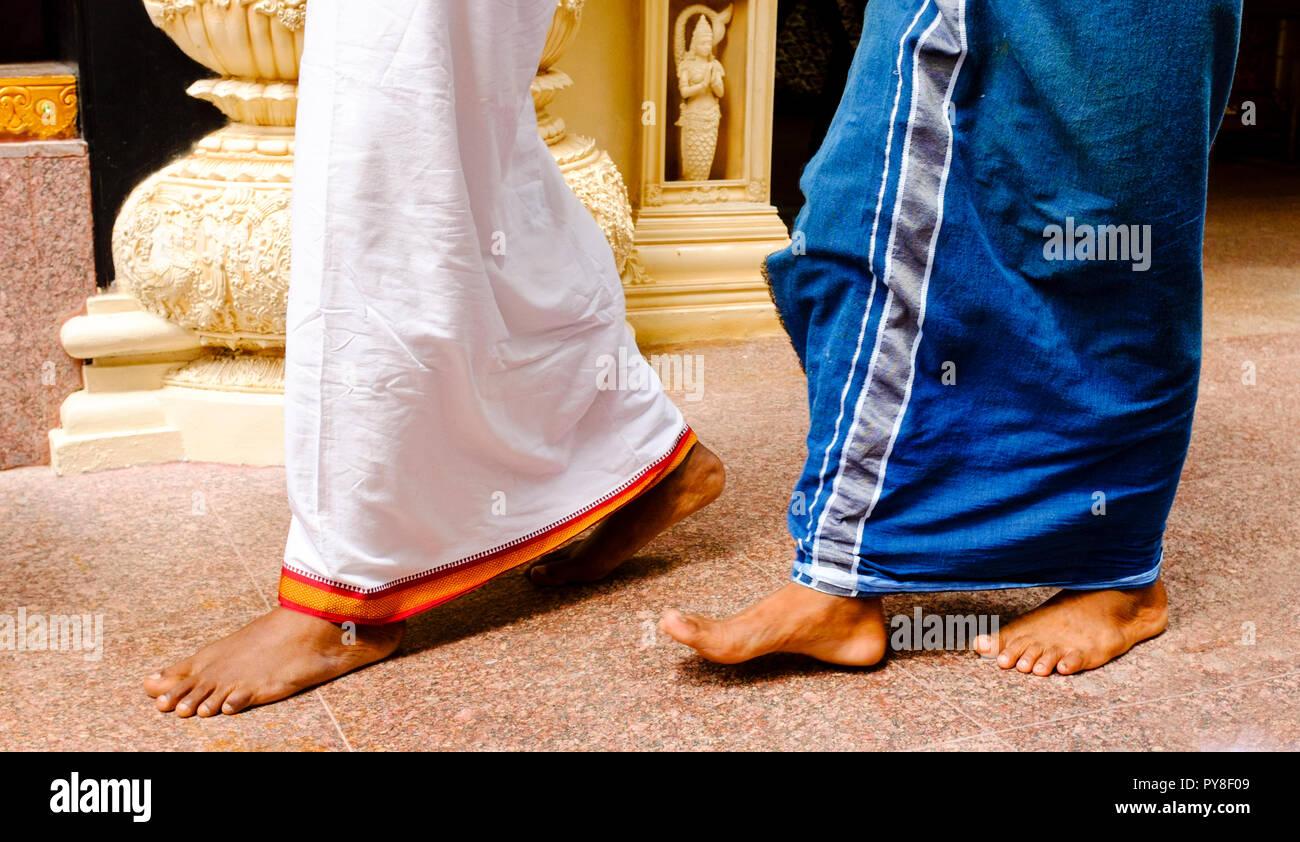 Hindu priests walking barefoot in temple, Singapore - Stock Image