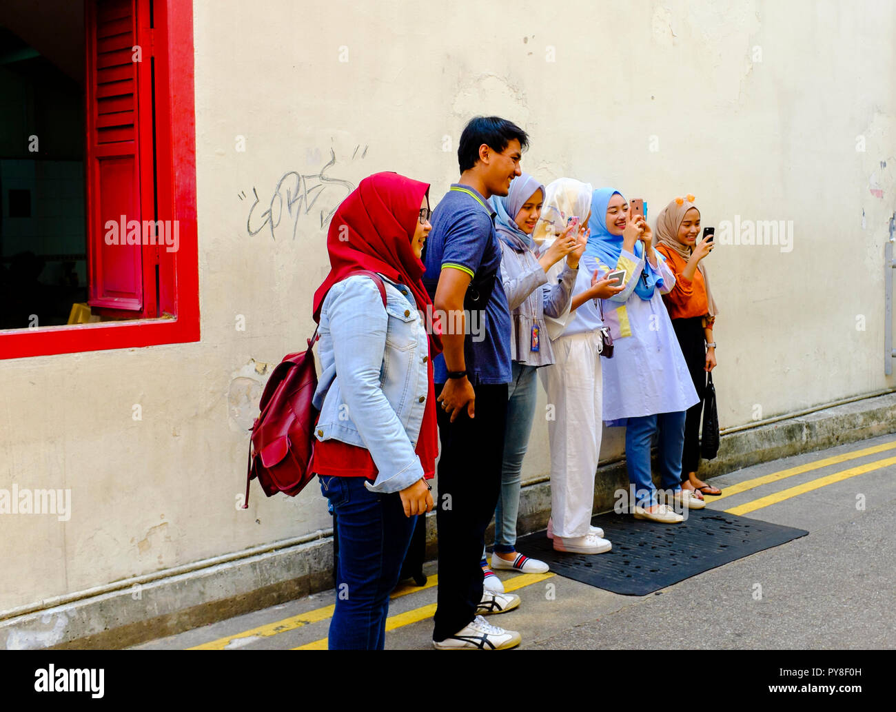 Group of smiling young people including muslim girls wearing hijabs using phones on street in Singapore - Stock Image