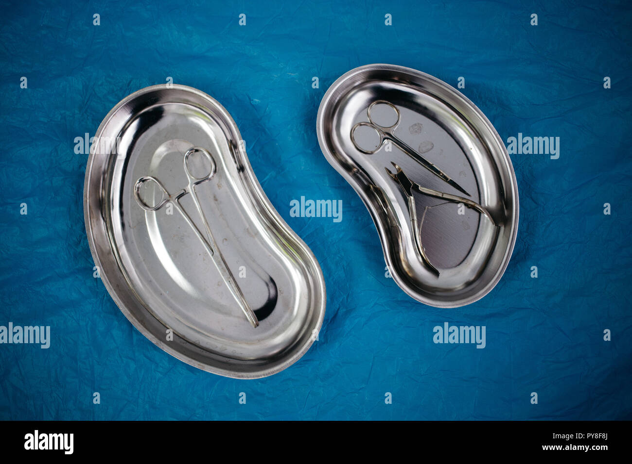 top view of medical instruments in the tray, disposable gloves on blue background. health, longevity Stock Photo