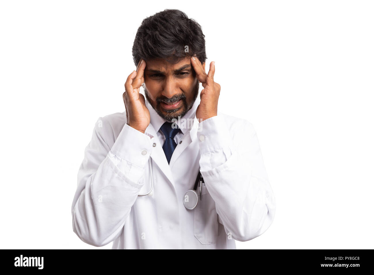 Indian doctor touching forehead with fingers as hurtful headache gesture isolated on white background - Stock Image