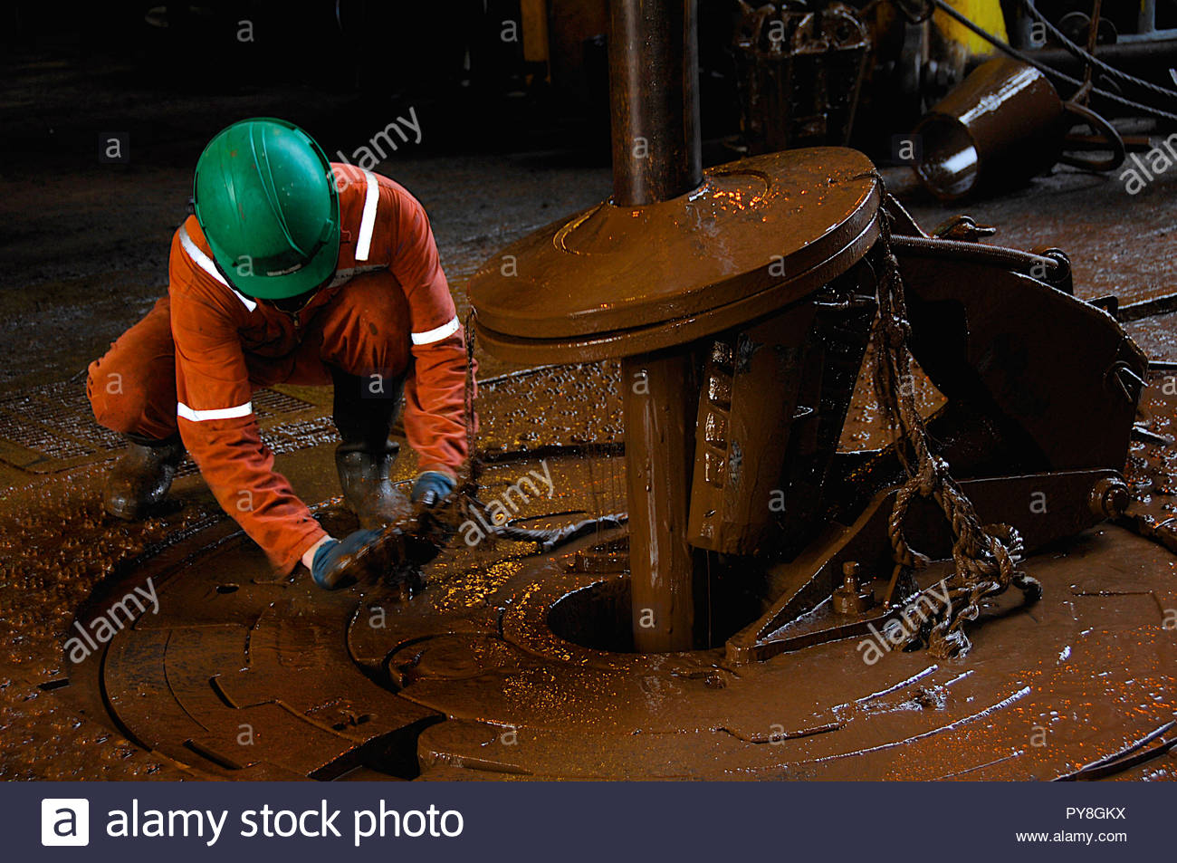 Worker crouched by dirty pipe - Stock Image