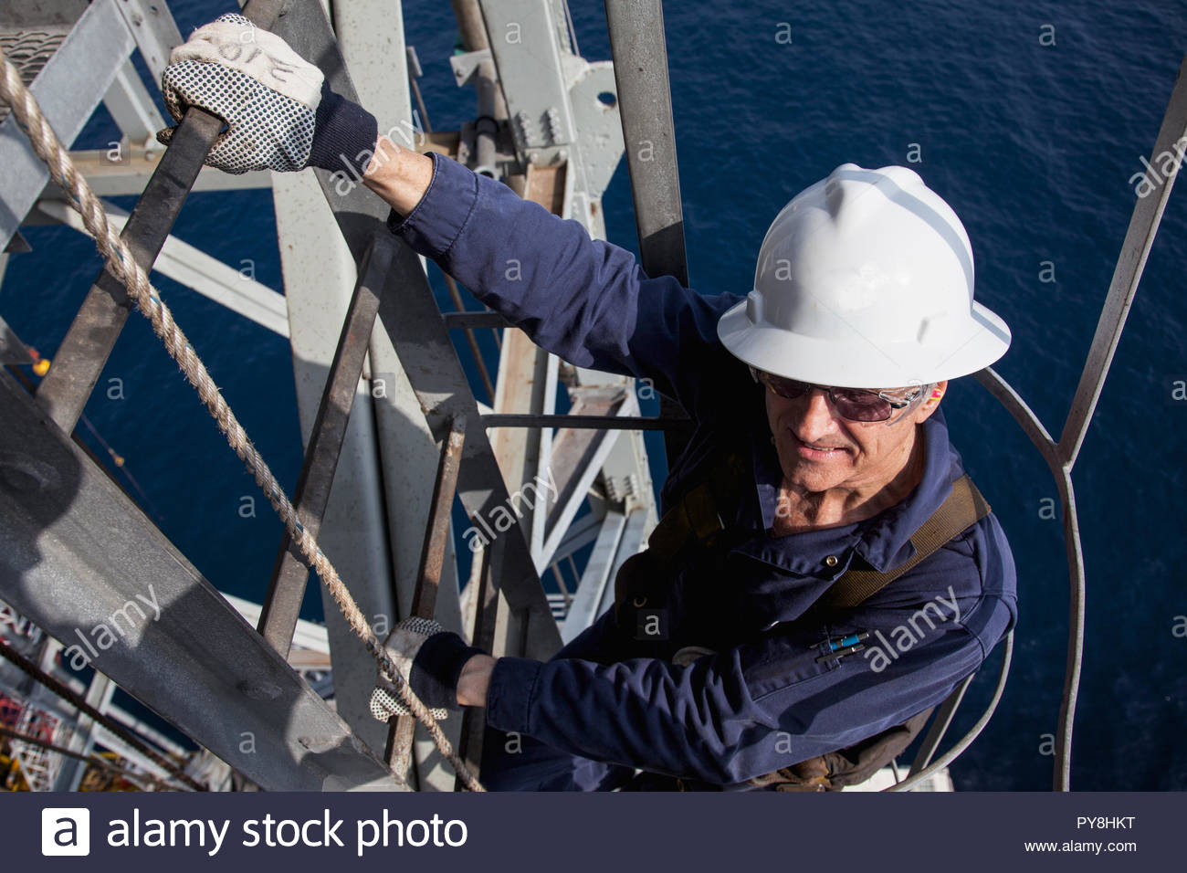 High angle view of worker on ladder of offshore oil platform - Stock Image