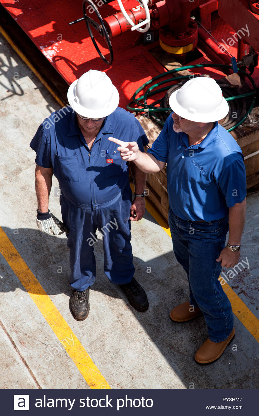 High angle view of workers pointing on offshore oil platform - Stock Image