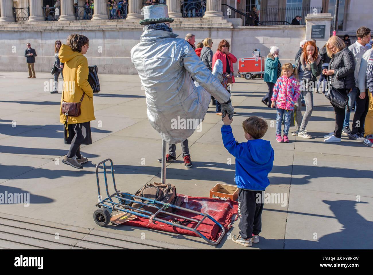 Man painted as a silver human statue in Trafalgar Square, London, England, UK. - Stock Image