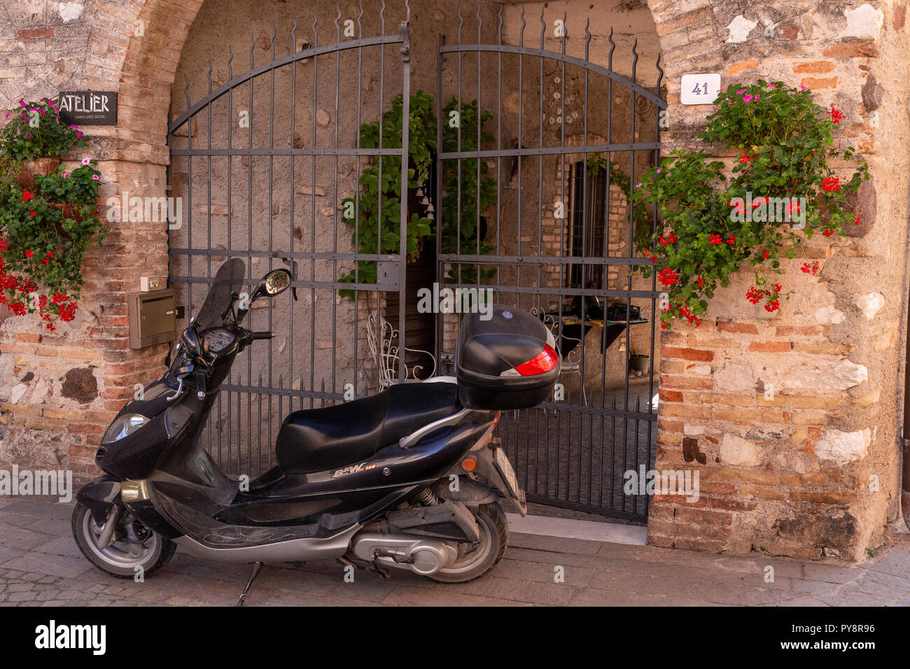 Scooter by a gate at Castellaro Laguselo in northern ItalyStock Photo