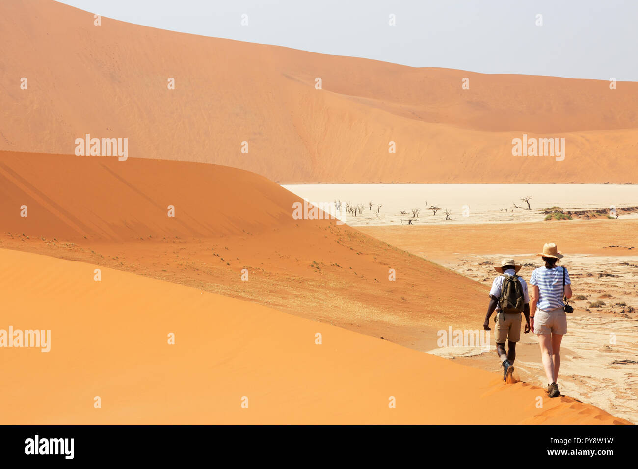 Namibia tourist - a tourtist being led by her tour guide through the sand dunes in Sossusvlei, Namib Desert, Namibia Africa - Stock Image