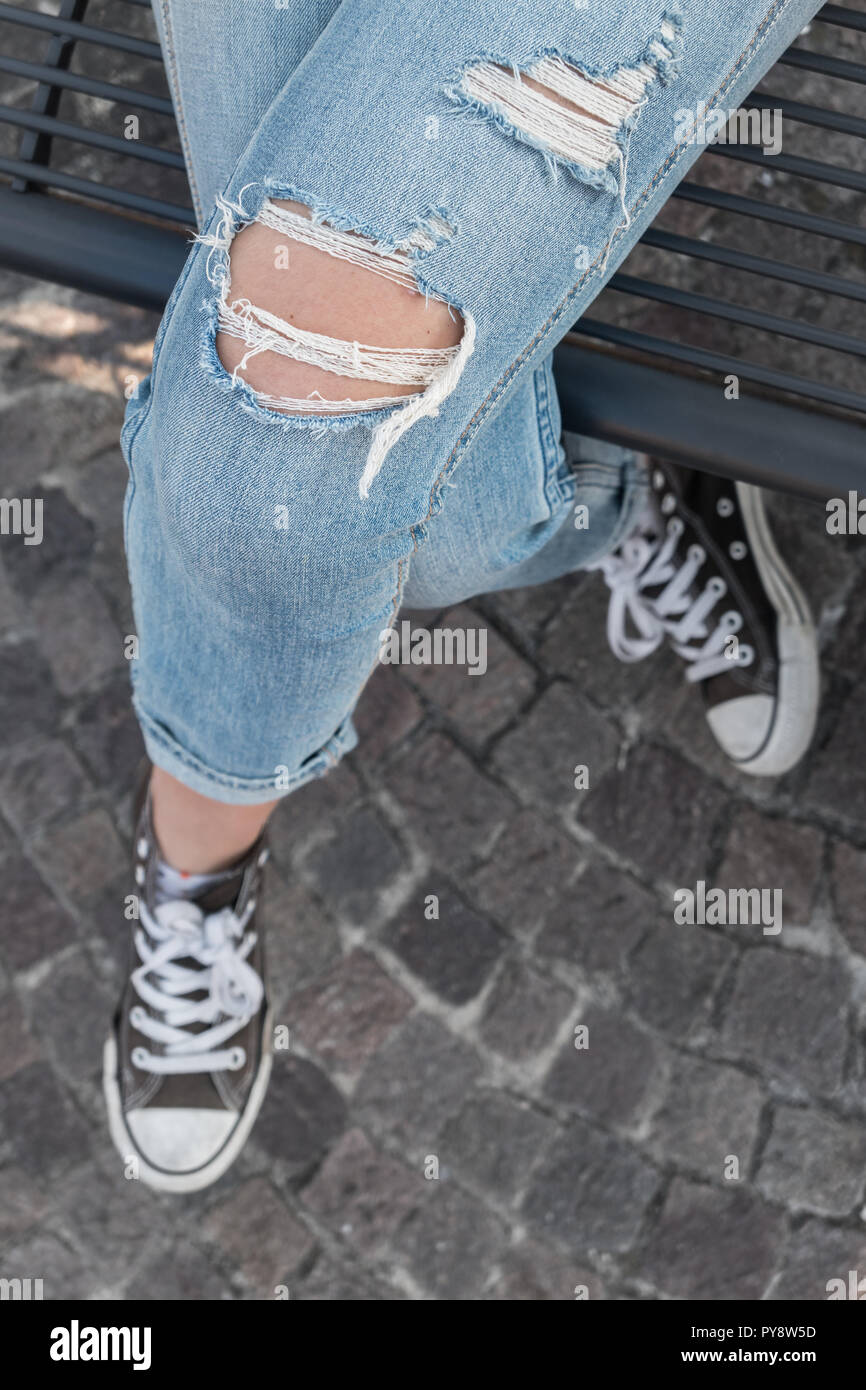 Woman wears trendy torn jeans and black shoes, she's sitting to legs crossed on the black bench. Seen from above. - Stock Image