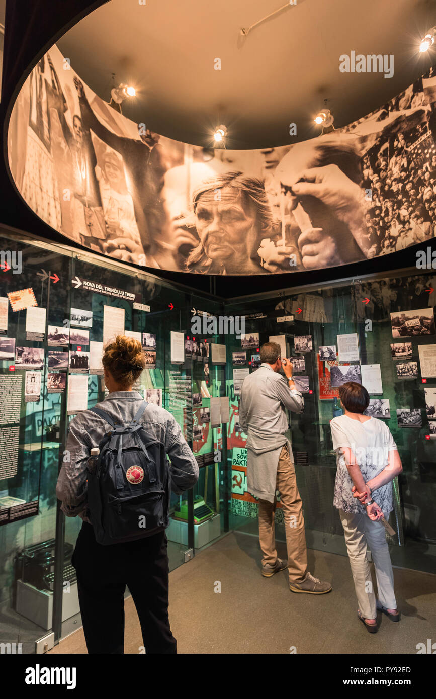 Vilnius Museum of Genocide Victims, view of visitors to the museum looking at Soviet surveillance equipment and artifacts, Lithuania. - Stock Image