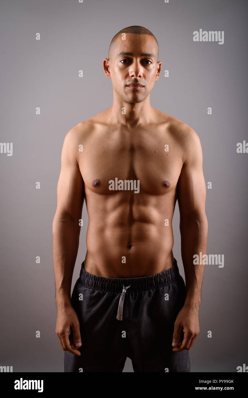 9179bb8502 Handsome bald man with six pack abs against gray background - Stock Image
