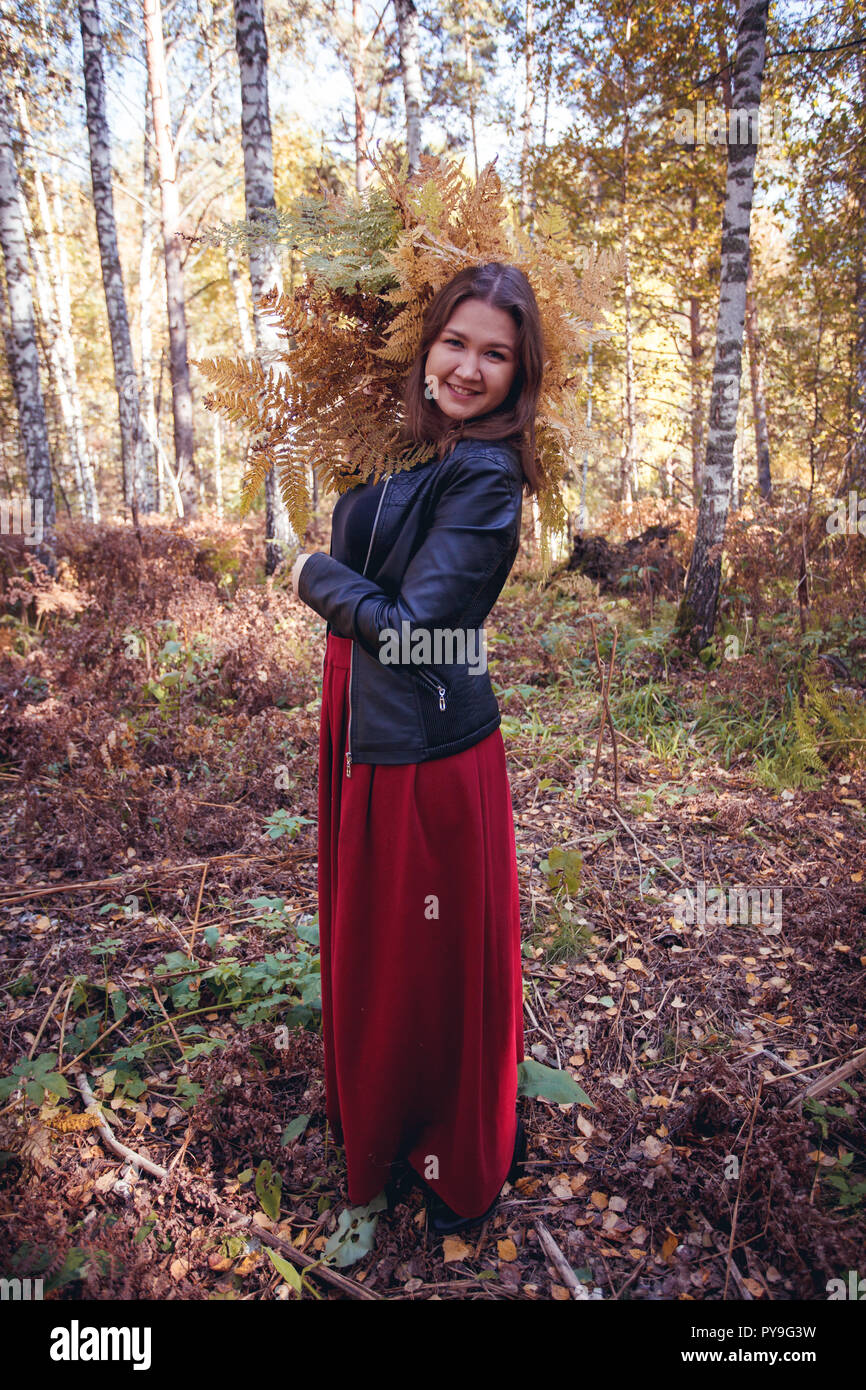 woman autumn portrait. cute girl outdoors with a bouquet of yellow fern in the forest, autumn fall concept Stock Photo