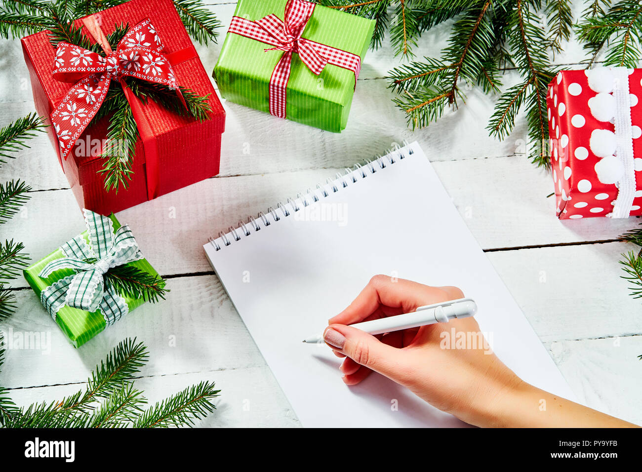 hand of a woman writing a letter to santa on an old white wooden table with christmas decorations Stock Photo