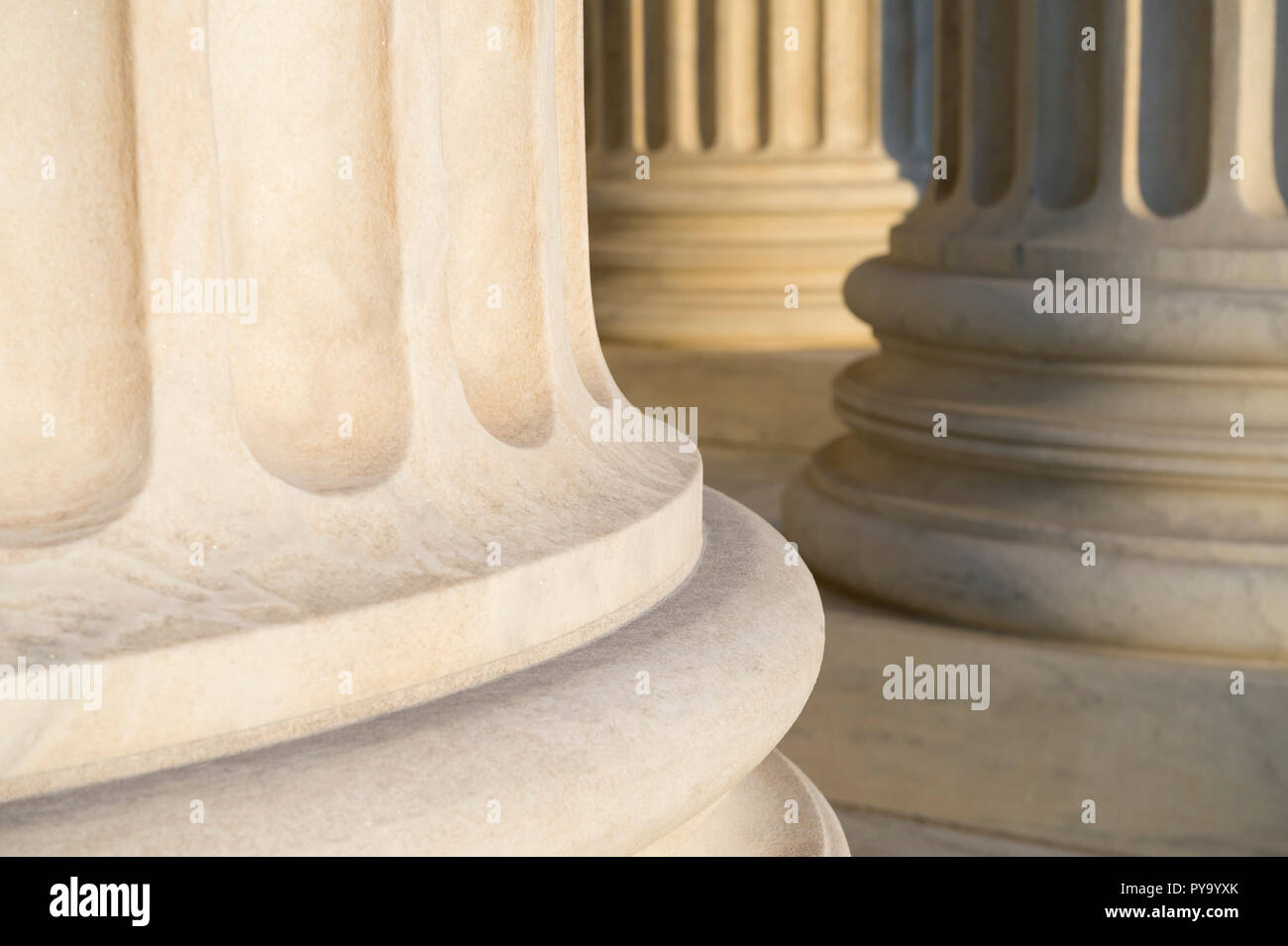 Lower detail of classical fluted columns in a colonnade in white marble lit by soft golden sunlight - Stock Image