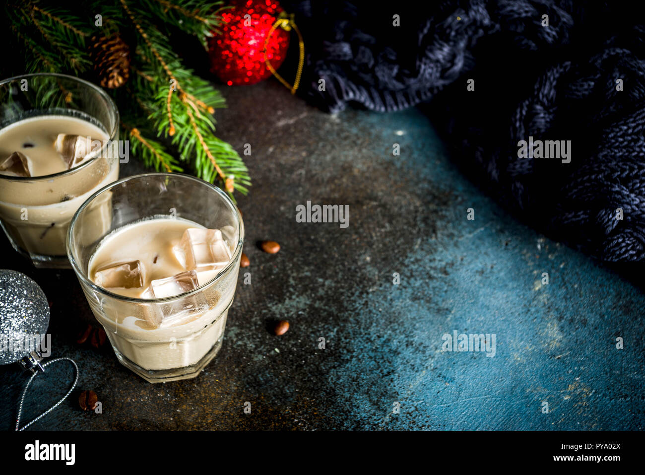 Irish cream cocktail or liqueur, traditional winter christmas drink, dark rusty background with fir tree branches, coffee beans and christmas decorati Stock Photo