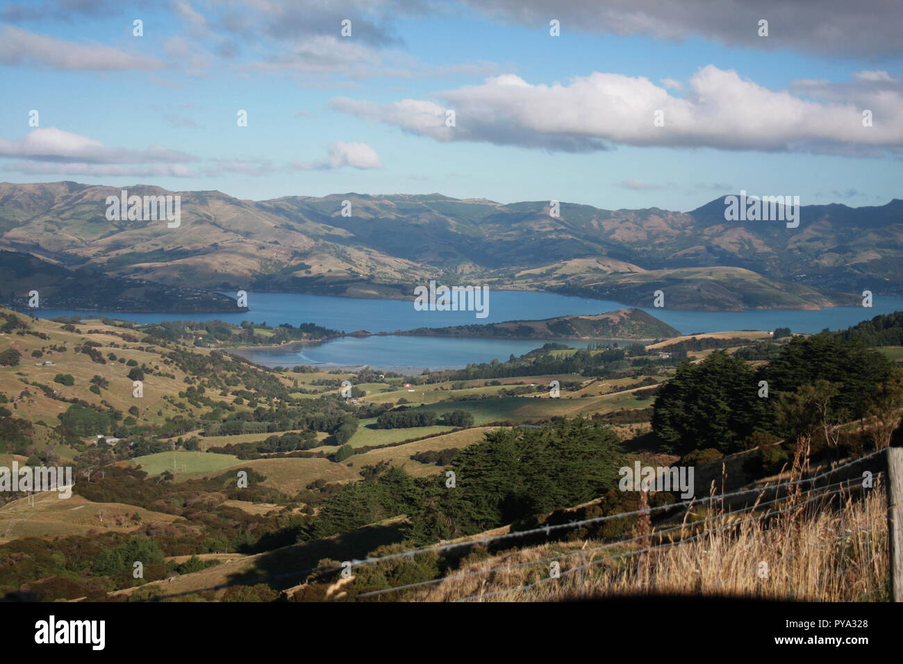 Looking over the Akaroa inlet towards Lushington Bay from the A75, with New Zealand hill farming land in the foreground. with a cloudy sky. - Stock Image