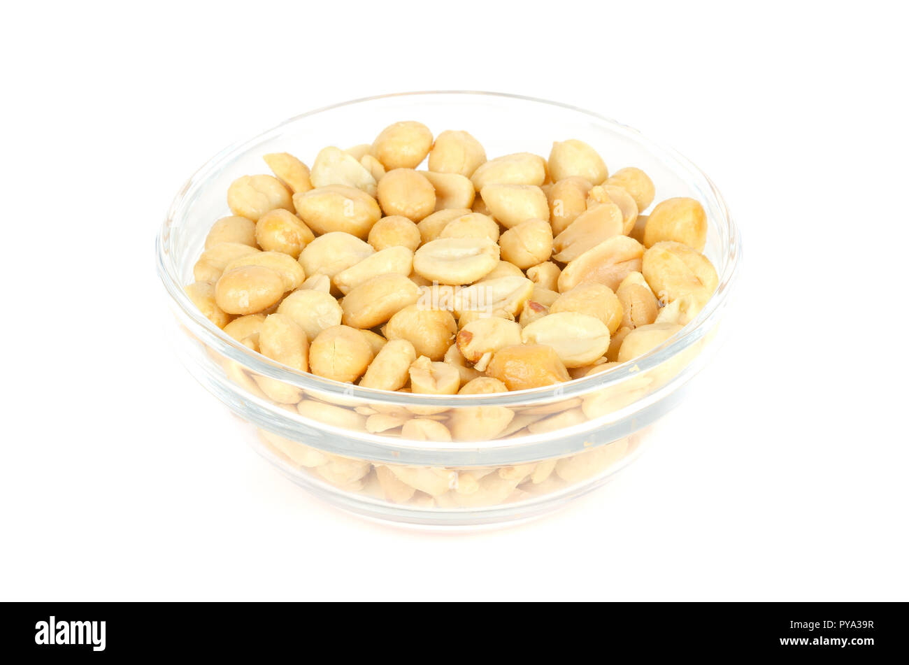 Roasted and salted peanuts in glass bowl. Shelled Arachis hypogaea, also called groundnut or goober, used as a snack. Isolated macro food photo. Stock Photo