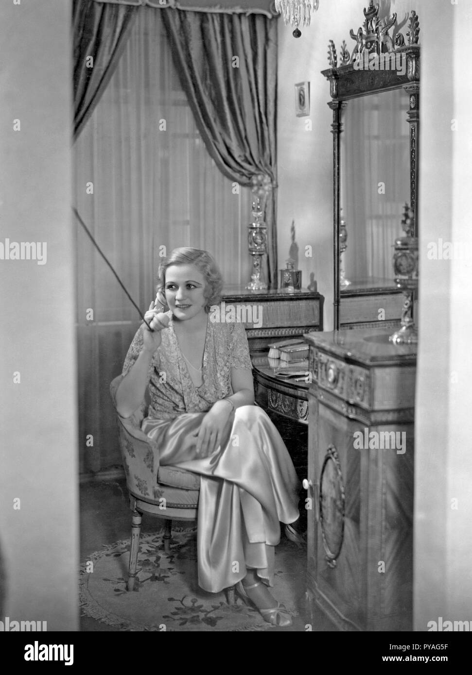 American actress in the 1930s. American actress Wynne Gibson, 1898-1987. She was contracted with movie company Paramount and made some 50 films between 1929 and 1956. Pictured here at home having a telephone conversation. 1930s - Stock Image