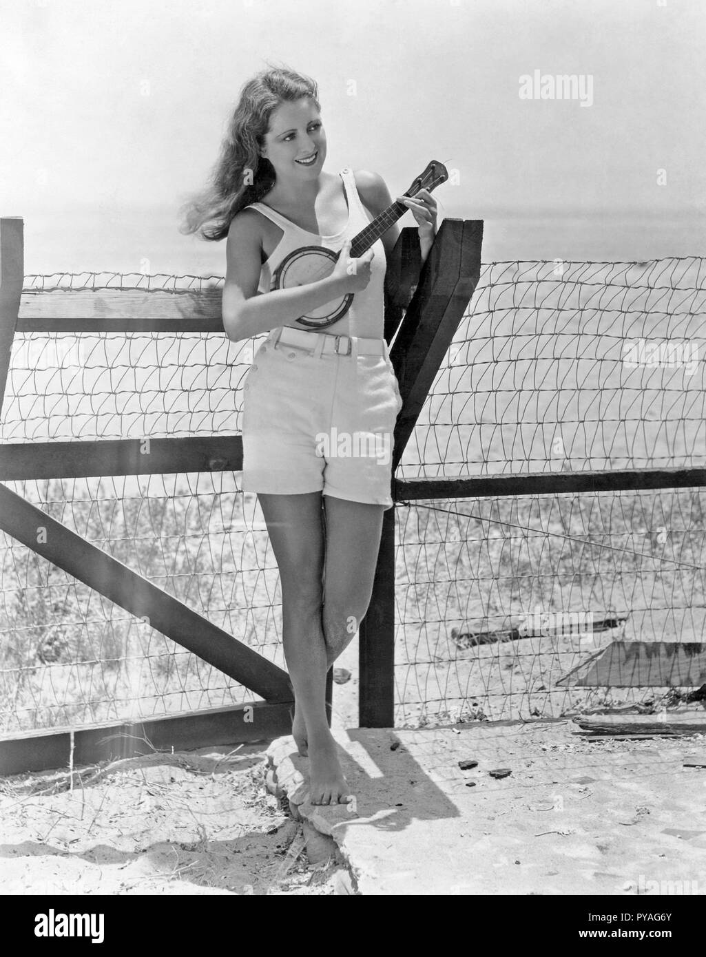 American actress in the 1930s. American actress Billie Dove, 1903-1997. On the beach playing an ukulele. Billie Dove was one of the more popular actresses in the silten films of the 1920s - Stock Image