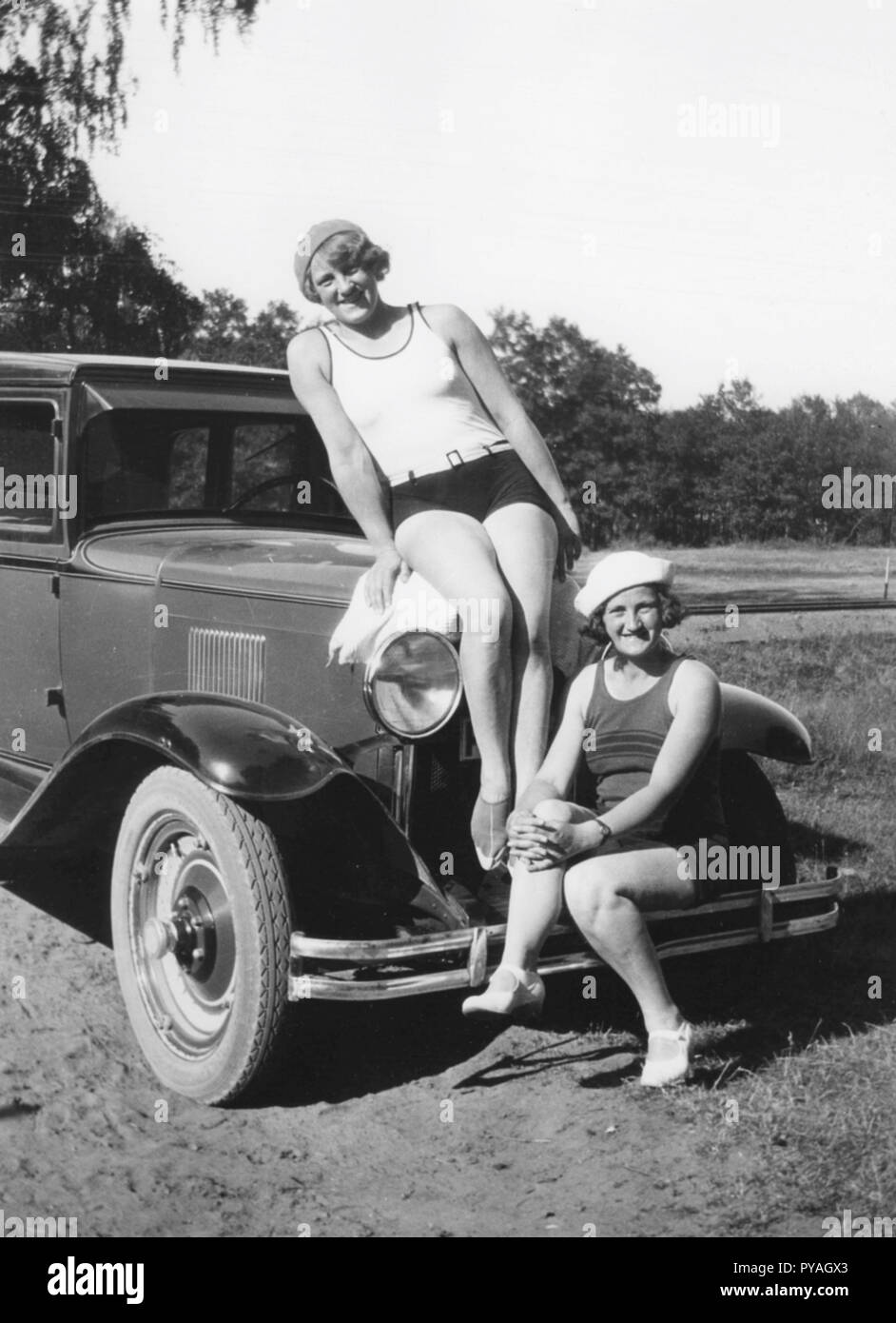 Fun in the 1930s. Two young women in bathing suits are sitting on the hood and front of a car. Sweden 1932 - Stock Image