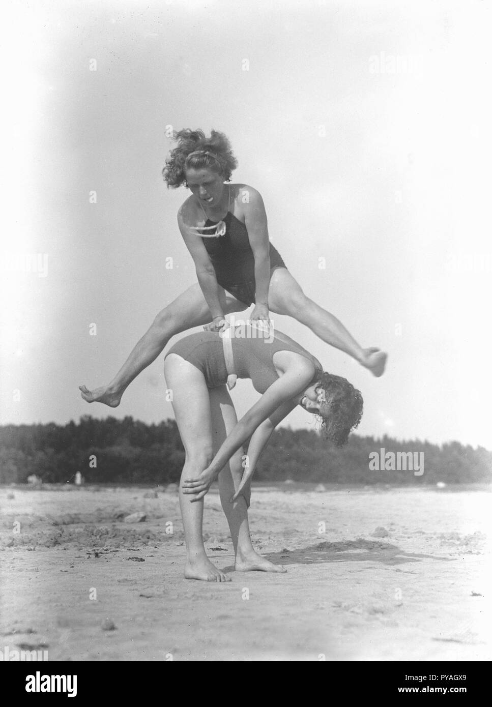 On the beach in the 1930s. Two women in bathing suits are playing around on the beach. Sweden 1939. Photo Kristoffersson ref 10-2 - Stock Image