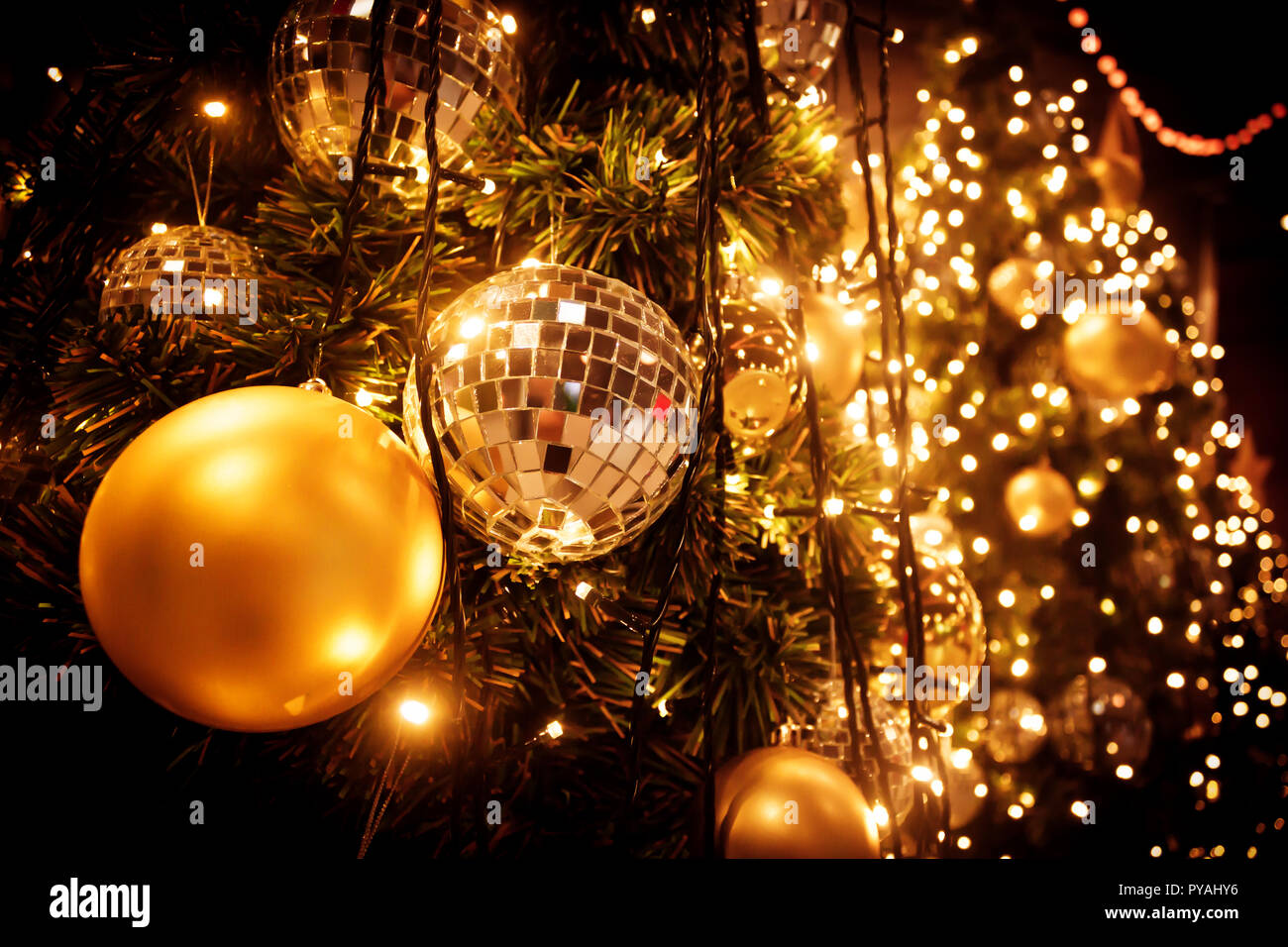 Christmas Tree With Gold Ball And Bokeh Lights Background Xmas Abstract Close Up With Glowing Decorations Outdoors
