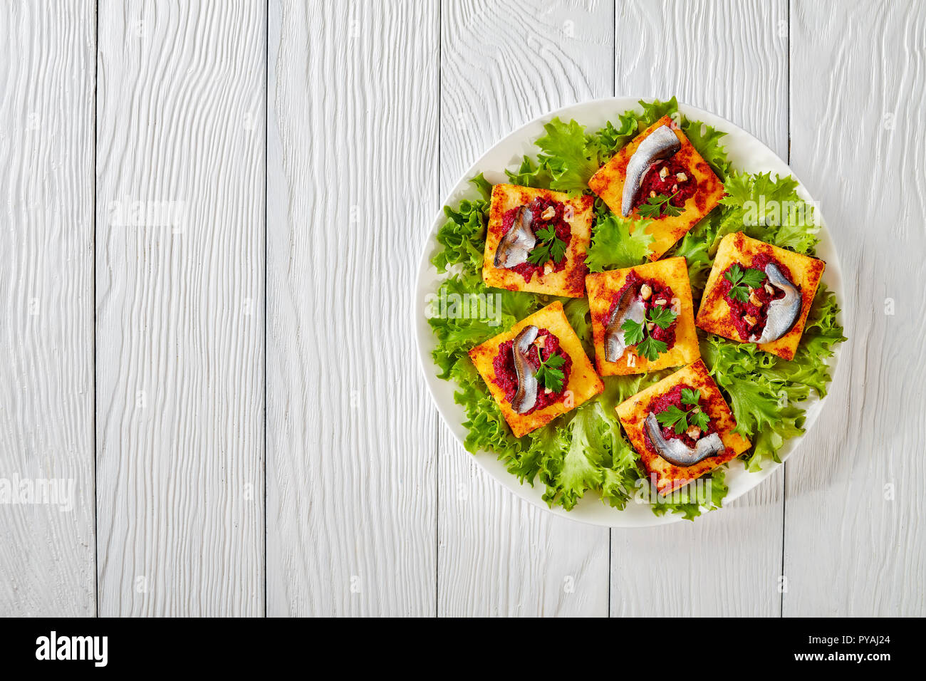 Fried Polenta Squares with Creamy beetroot puree, topped with anchovies on a white plate on a wooden table, horizontal view from above Stock Photo