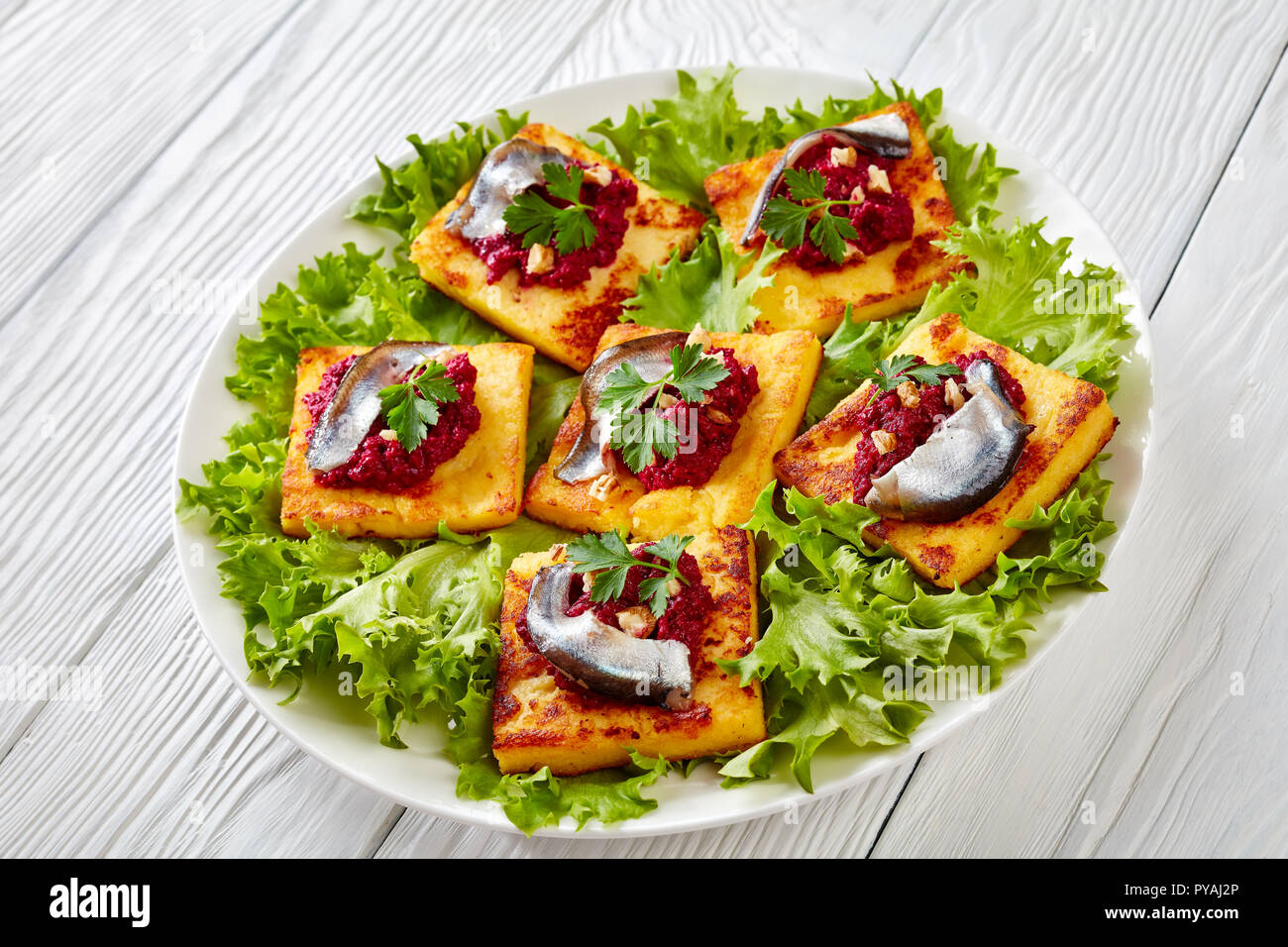 tasty Fried Polenta Squares with Creamy beetroot puree, topped with anchovies and garnished with fresh parsley on a white plate on a wooden table, hor - Stock Image