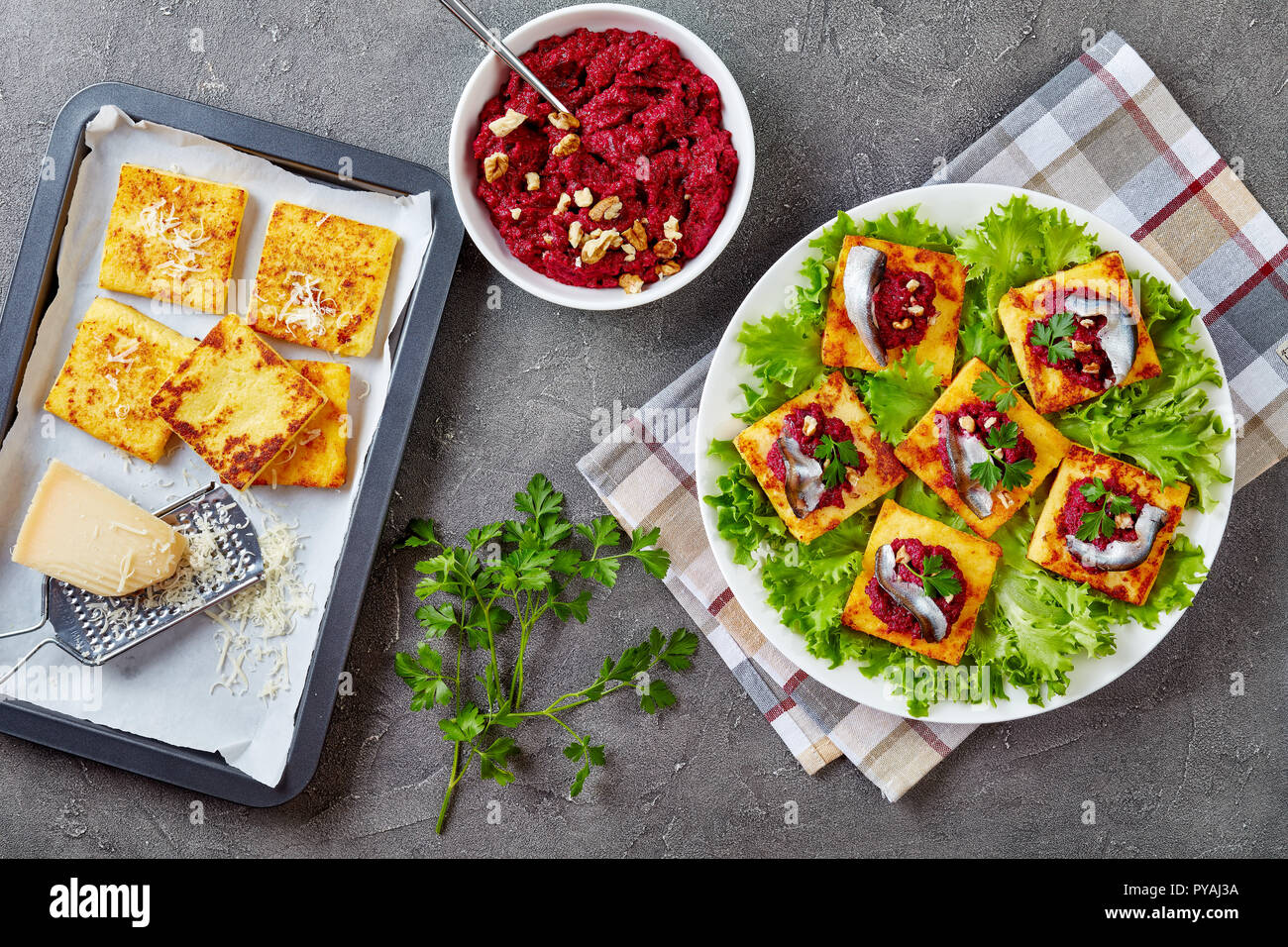 Polenta Squares with Creamy beetroot puree, topped with anchovies and parsley on a white plate. freshly baked polenta bars and parmesan on a baking tr - Stock Image